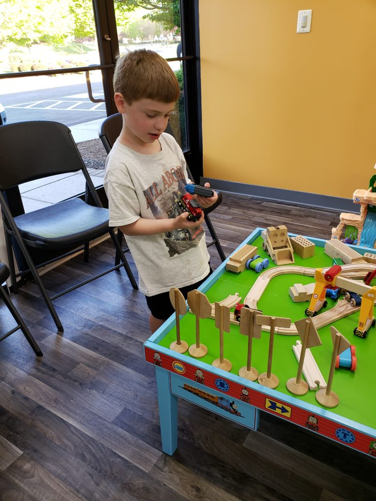 Child playing with train table at indoor play center