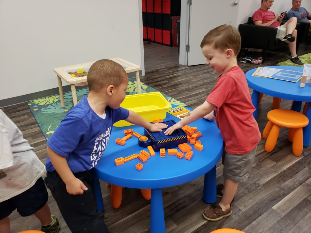 Children playing with earthquake simulator at indoor play center