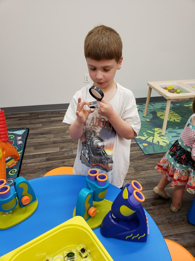 Child looking at insect through magnifying glass at indoor play center